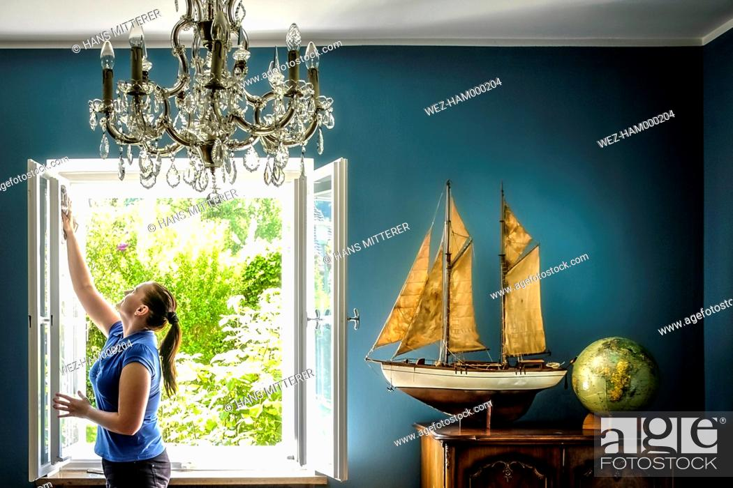 Imagen: Home interior with vintage ship model and globe, woman cleaning windows.