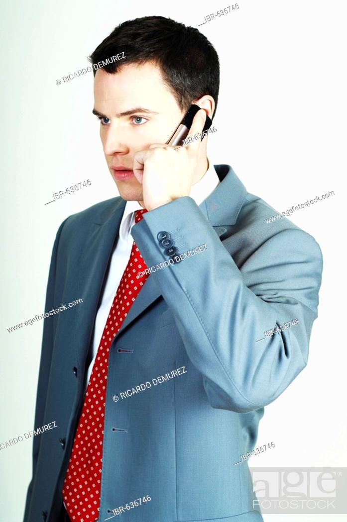 Stock Photo: Young businessman making a call with his mobile phone.