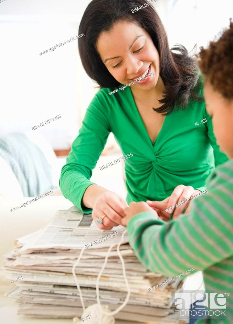 Stock Photo: Mixed race mother and son recycling newspapers.