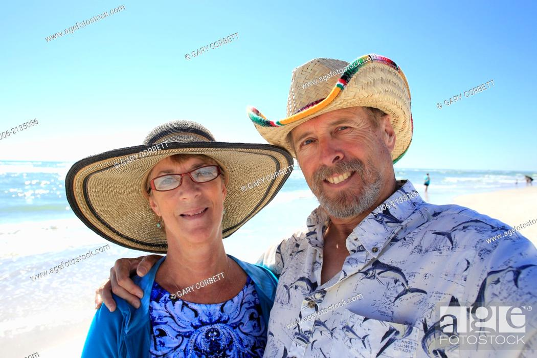 Stock Photo: a senior couple smiling for the camera at a beach.