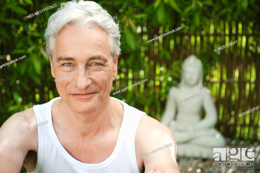 Stock Photo: Germany, Bavaria, Mature man smiling with buddha statue in background.