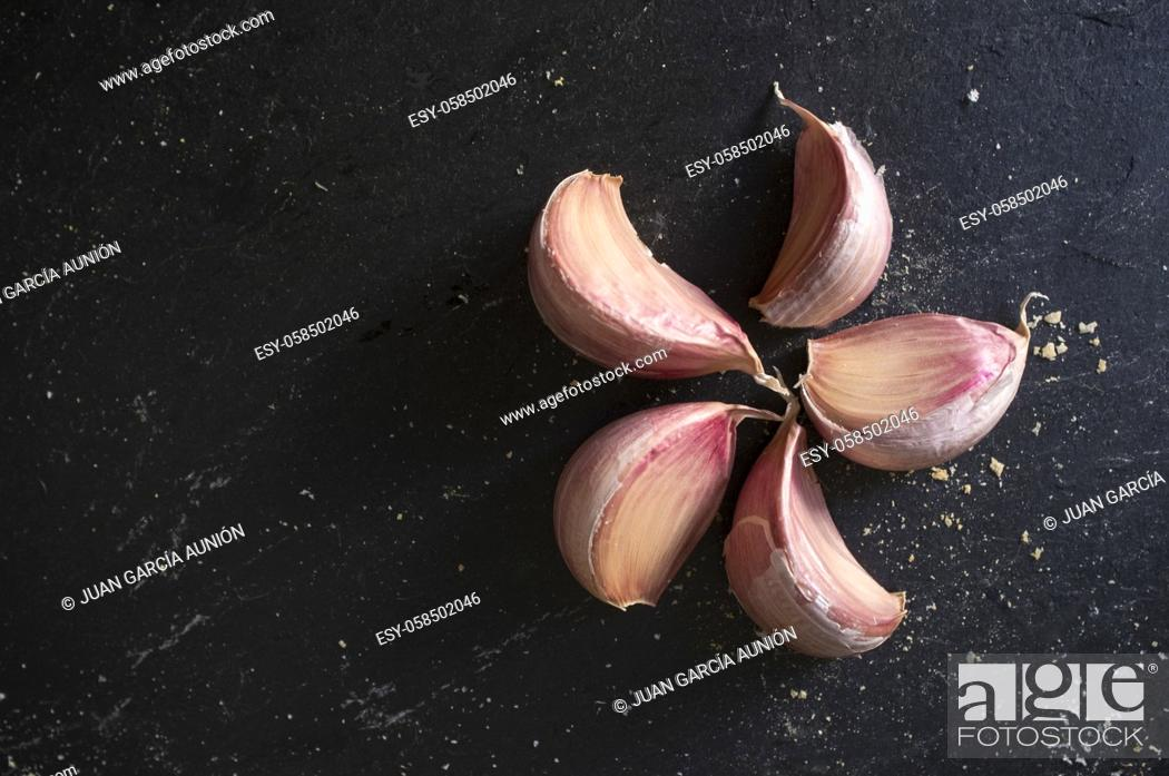 Stock Photo: Spanish pink cloves of garlic. Isolated over black slate with covered with bread crumbles.