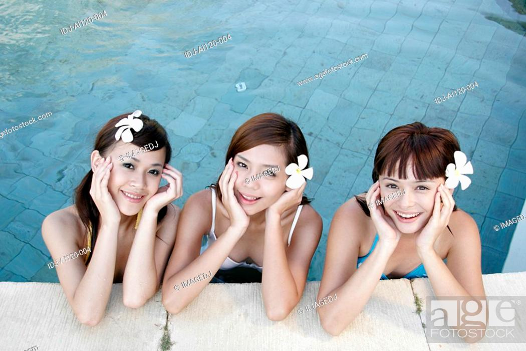 Stock Photo: Portrait of three teenage girls in swimming pool.