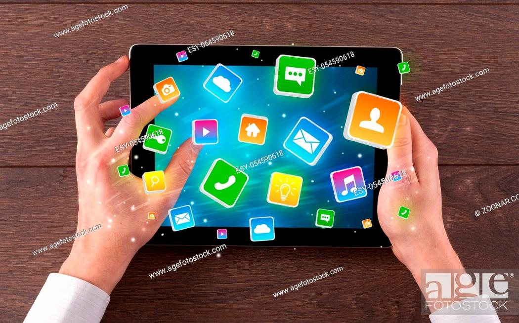 Stock Photo: Hand using tablet with colourfull bounce application symbols and icons concept.