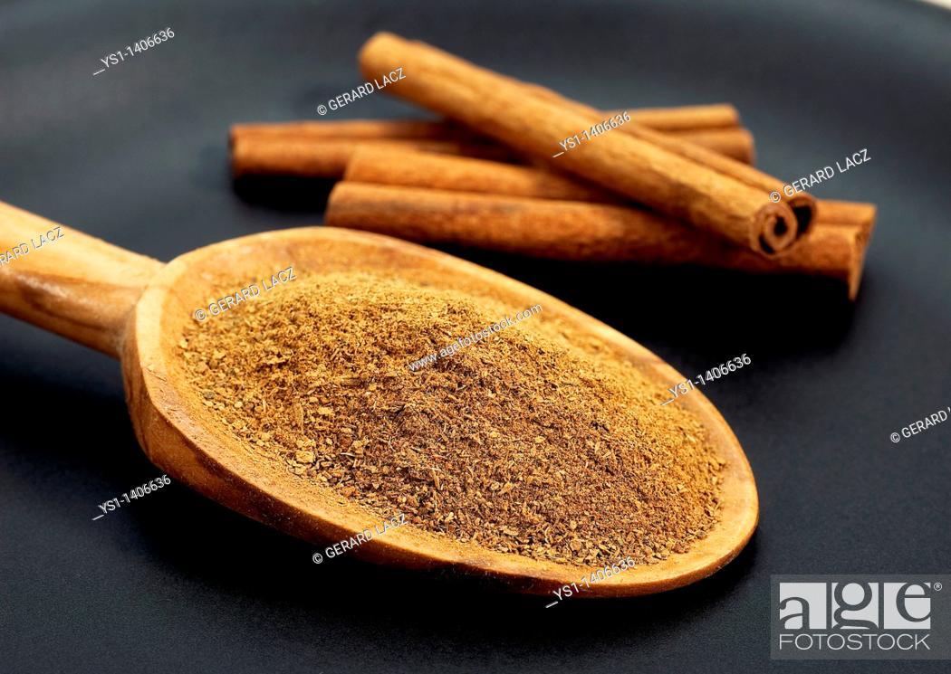 Stock Photo: CINNAMON BARK AND POWDER cinnamomum zeylanicum AGAINST BLACK BACKGROUND.