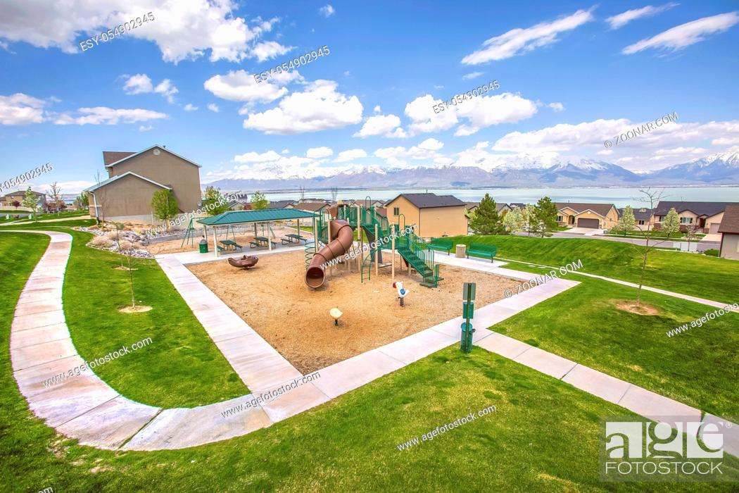 Stock Photo: Playground and picnic area with beautiful homes and lake in the background. The park has a picturesque view of snow capped mountain under cloudy sky.