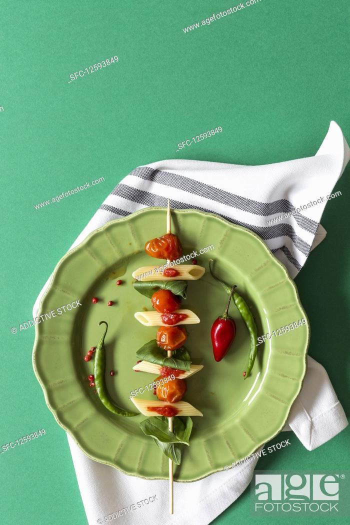 Stock Photo: Macaroni with tomato sauce on green background.