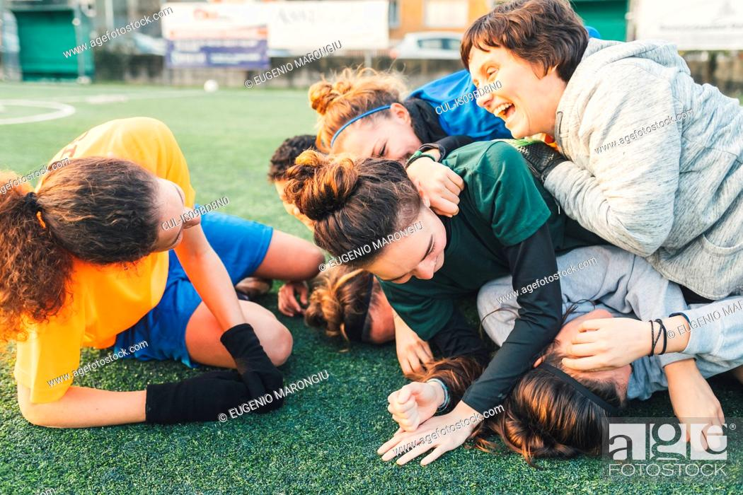 Stock Photo: Football players jubilant and hugging on pitch.