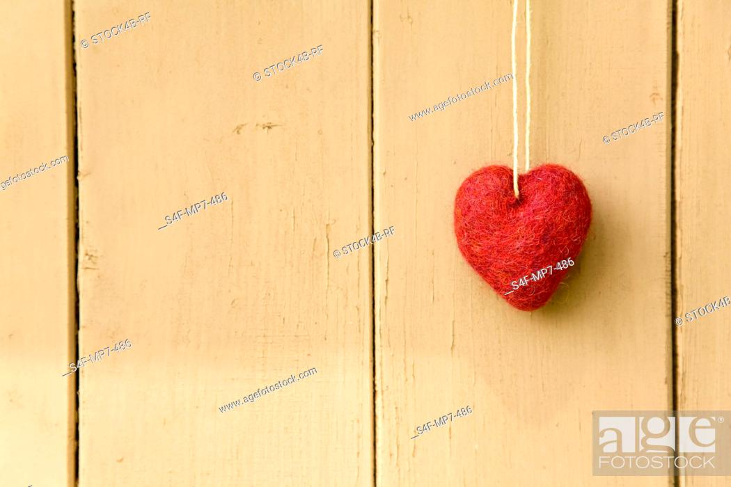 Stock Photo: Red heart hanging at wooden wall.