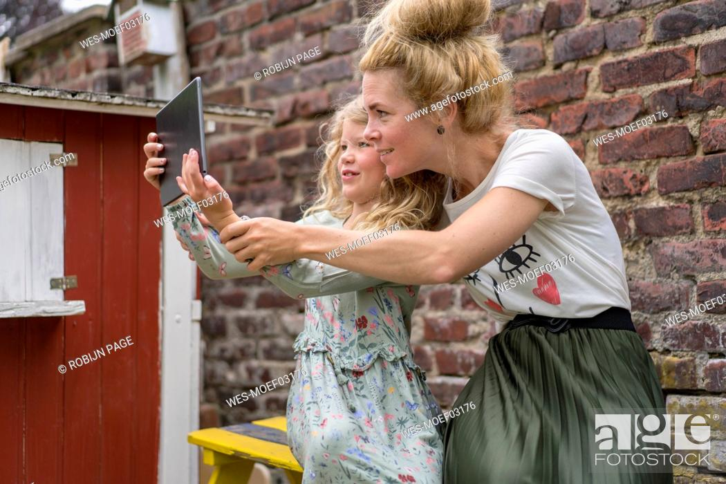 Stock Photo: Smiling girl taking selfie with mother through digital tablet against brick wall at back yard.