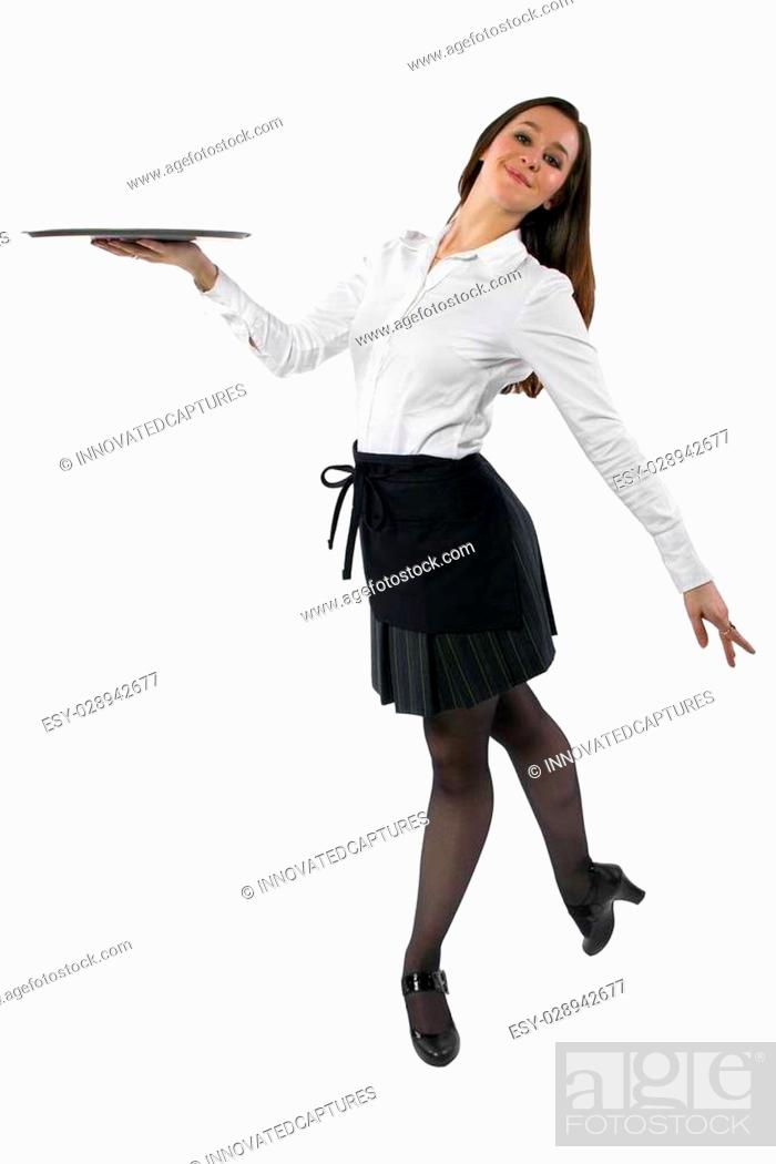 Photo de stock: young female waitress dancing and carrying an empty tray.