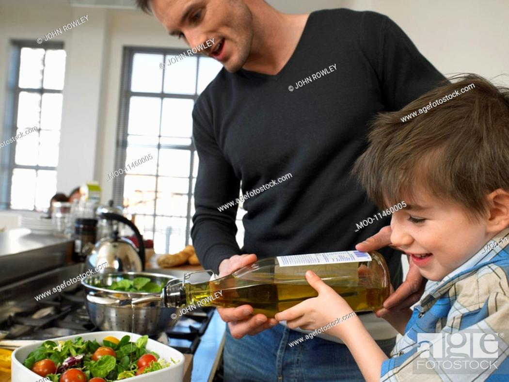 Stock Photo: Father and son 3-4 preparing salad in kitchen.