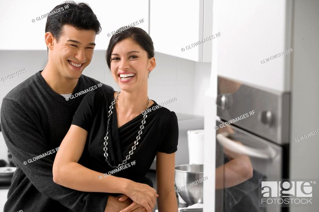 Stock Photo: Young couple smiling in the kitchen.