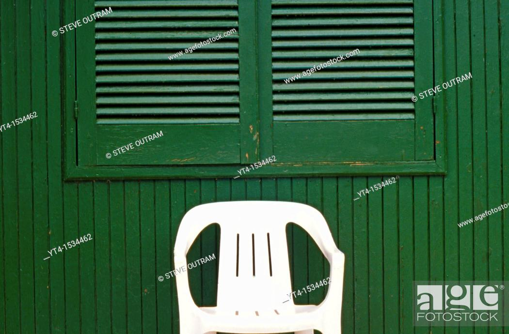 Stock Photo: White Plastic Chair in front of Green Hut.