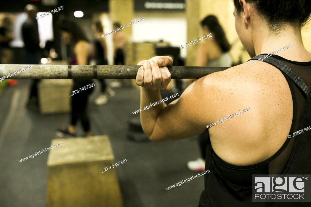 Stock Photo: Woman Bodybuilder with heavy barbbells in gym.
