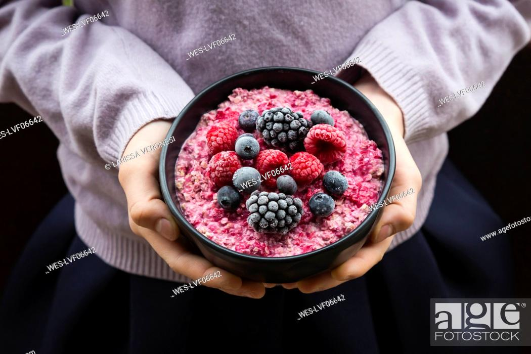 Stock Photo: Girl holding bowl with overnight oats mit frozen berries.