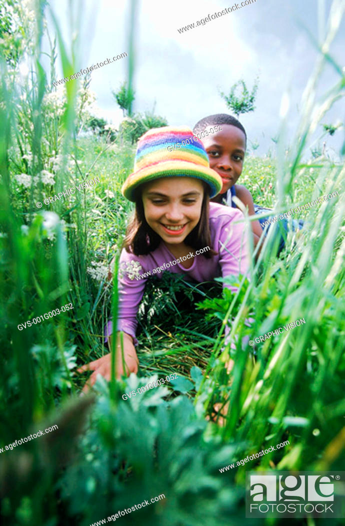 Stock Photo: Young children lying in the grass smiling.