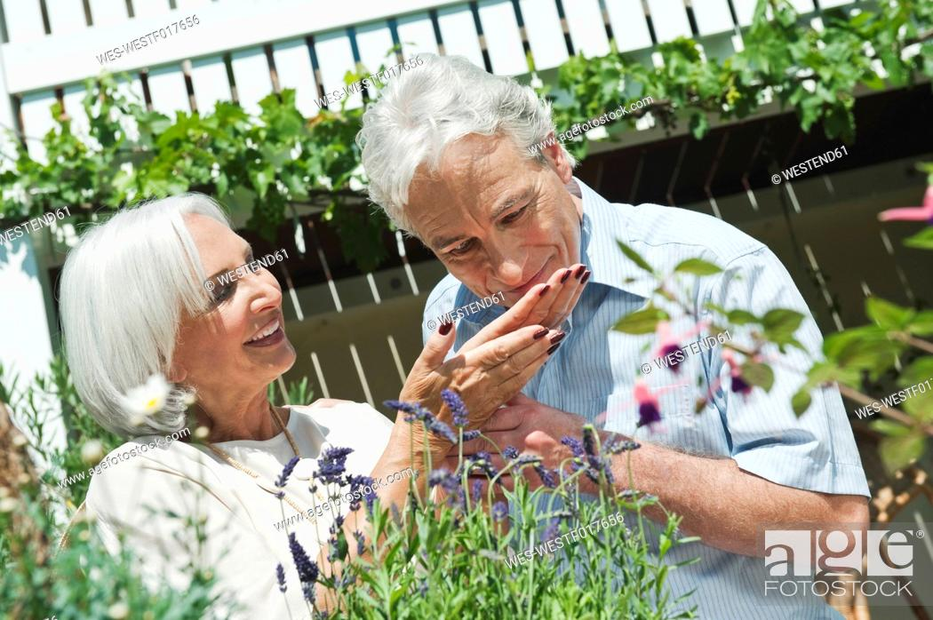 Stock Photo: Germany, Bavaria, Mature man and senior woman in garden, smiling.