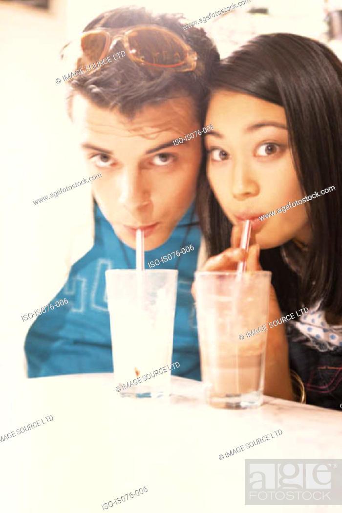 Stock Photo: Couple drinking milkshakes.