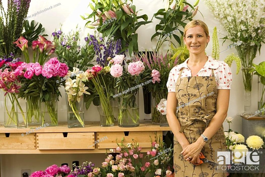 Stock Photo: Florist in apron standing in front of display in flower shop, smiling, front view, portrait.