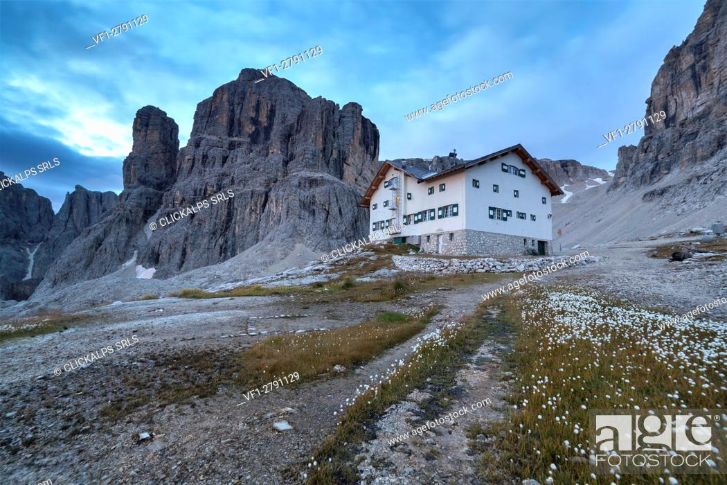 Stock Photo: Europe, Italy, South Tyrol, Bolzano. Rifugio Franco Cavazza at Pisciadu in the Sella group with carpet of cotton grass in the foreground, Dolomites.
