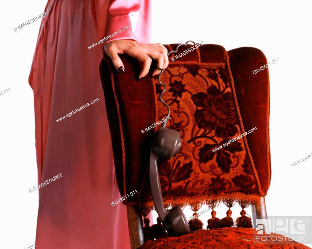 Stock Photo: Woman dangling telephone handset over chair.