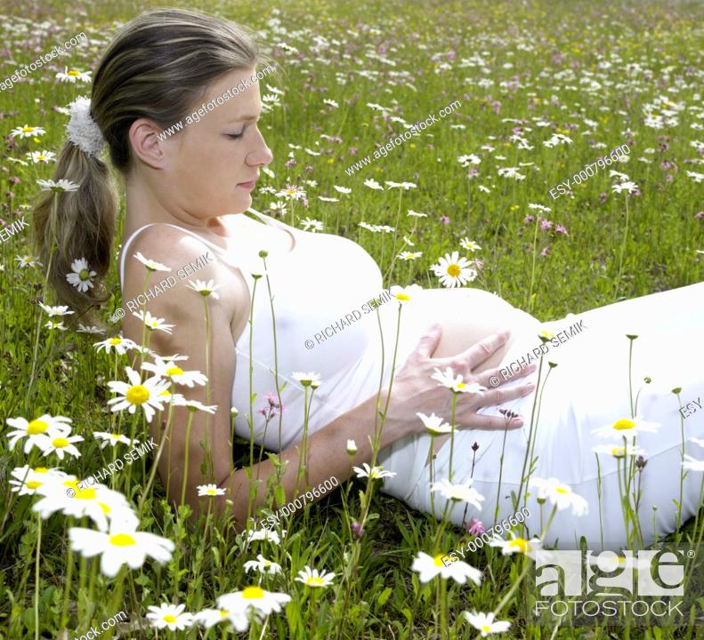 Stock Photo: pregnat woman on meadow.