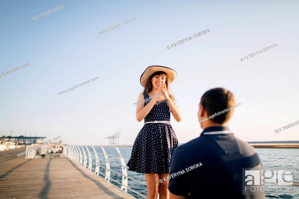 Stock Photo: Man proposing to woman on pier.
