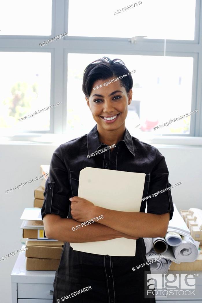 Stock Photo: Businesswoman holding folder in office.
