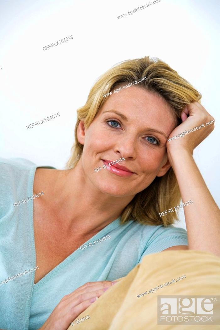 Stock Photo: Mature woman sitting on sofa, smiling, looking at camera, portrait.