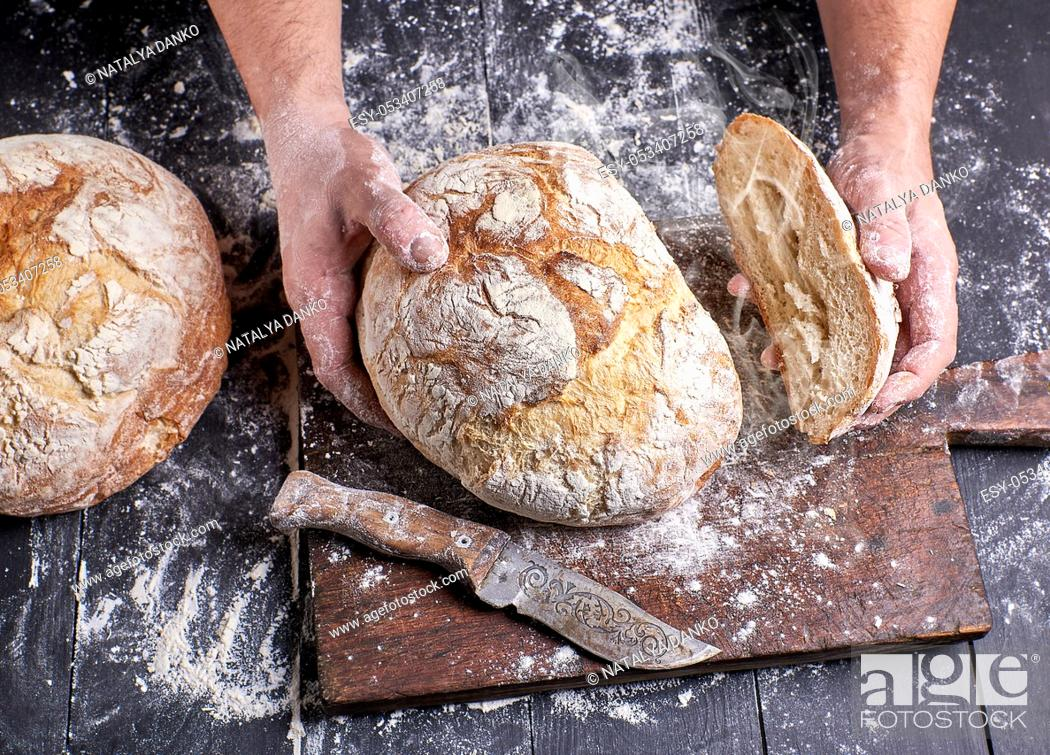 Stock Photo: chef in a black uniform holding fresh hot baked round bread over the table in his hands.