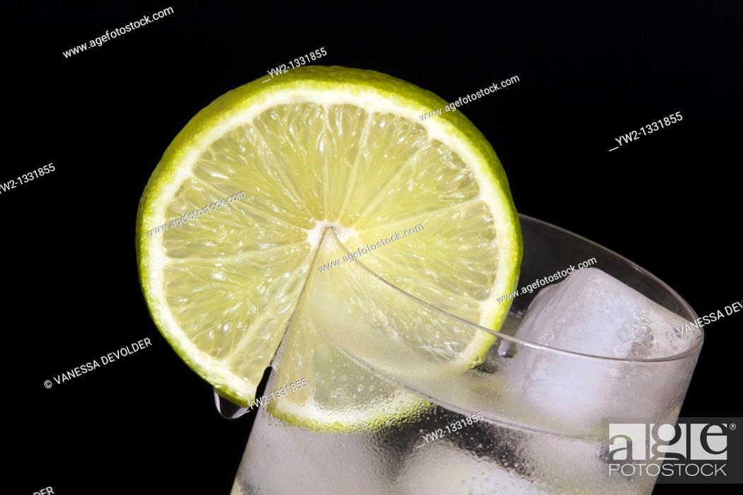 Stock Photo: Lime slice on a glas  Studio photograph, black background  V10BEL0514.