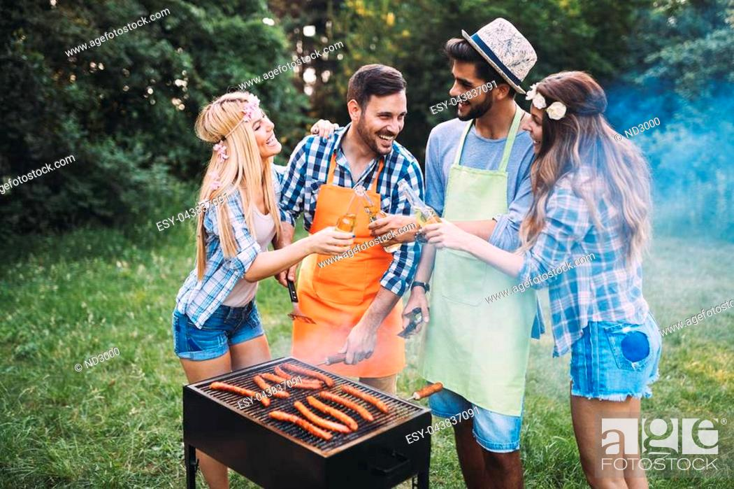 Stock Photo: Cheerful friends spending time in nature and having barbecue.