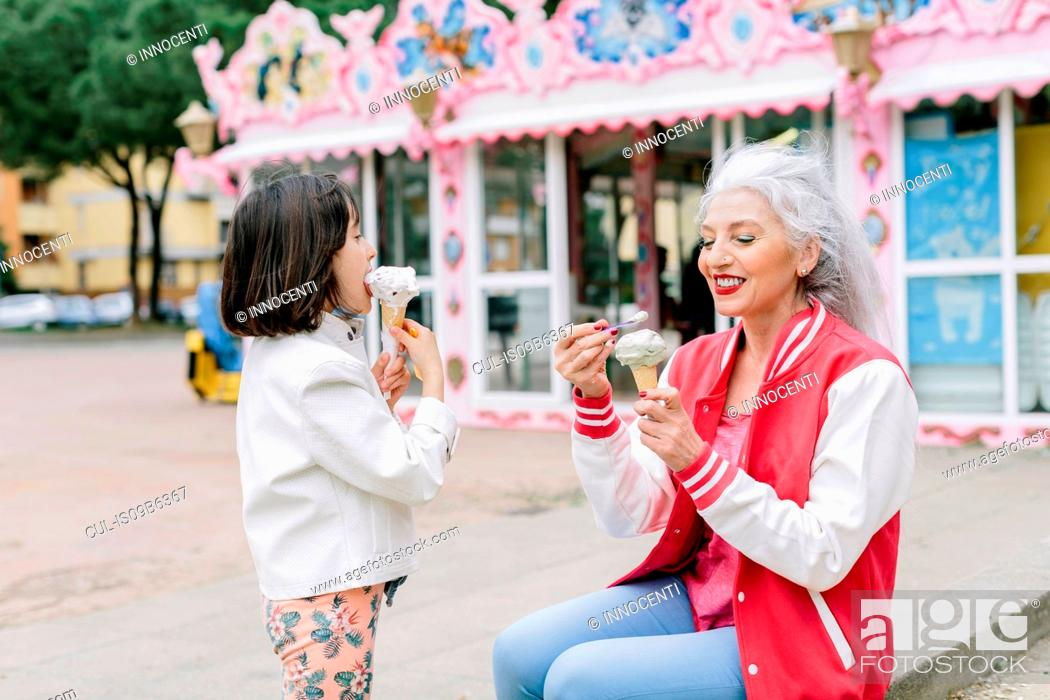 Imagen: Mature woman and girl eating ice cream cones outside ice cream parlour, Florence, Italy.