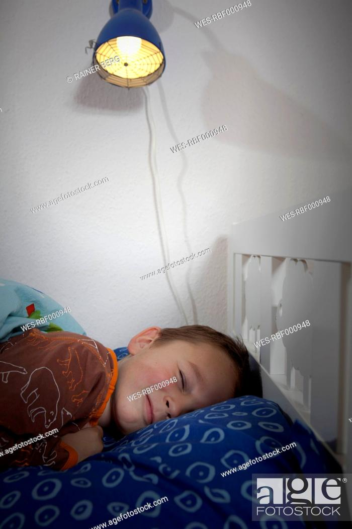 Stock Photo: Germany, Berlin, Boy sleeping on bed.
