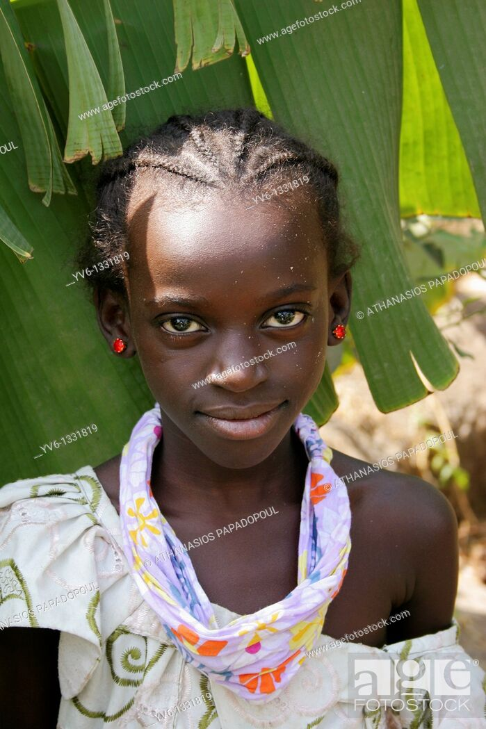 Stock Photo: Portrait of an African girl with white spots on her face looking at the lens with banana leafs as background, Tanji Village, Tanji, Gambia, Africa.