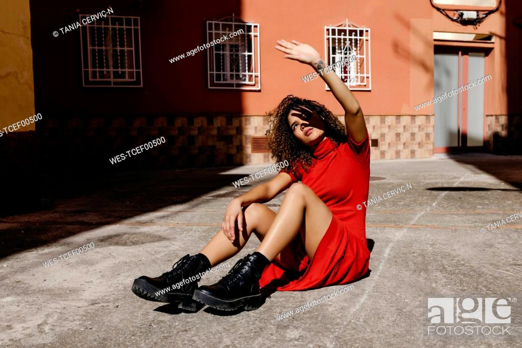 Stock Photo: Young woman wearing red dress and sitting on ground, lifting her hand against sunlight.