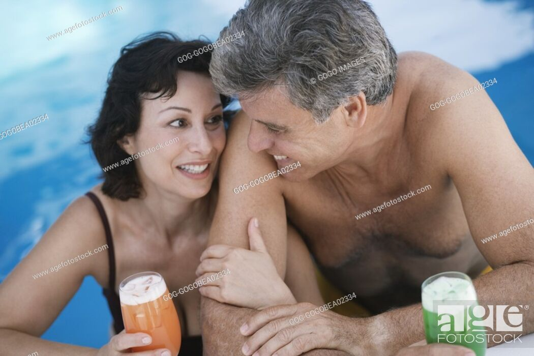 Stock Photo: Couple having tropical drinks in pool.