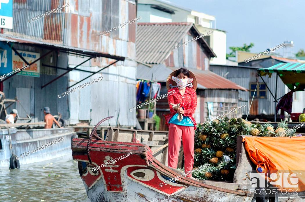 Stock Photo: Vietnam, Can Tho, market woman on a boat loaded with pineapples in the Mekong Delta.