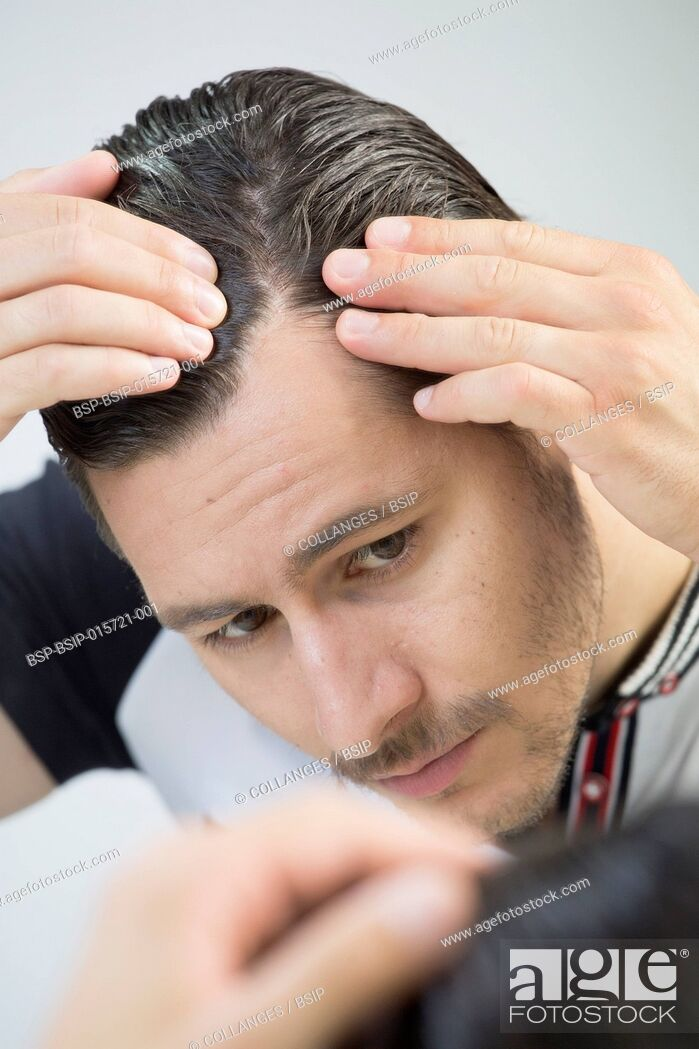 Stock Photo: Man looking in a mirror.