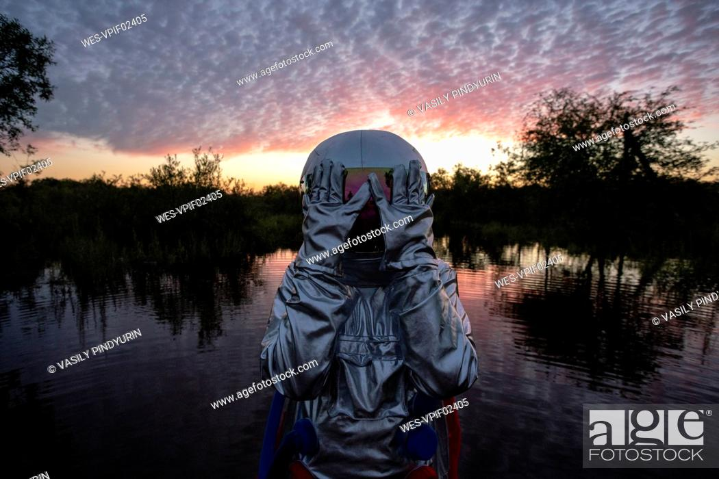 Stock Photo: Portrait of spacewoman standing in water at sunset, hands covering helmet.