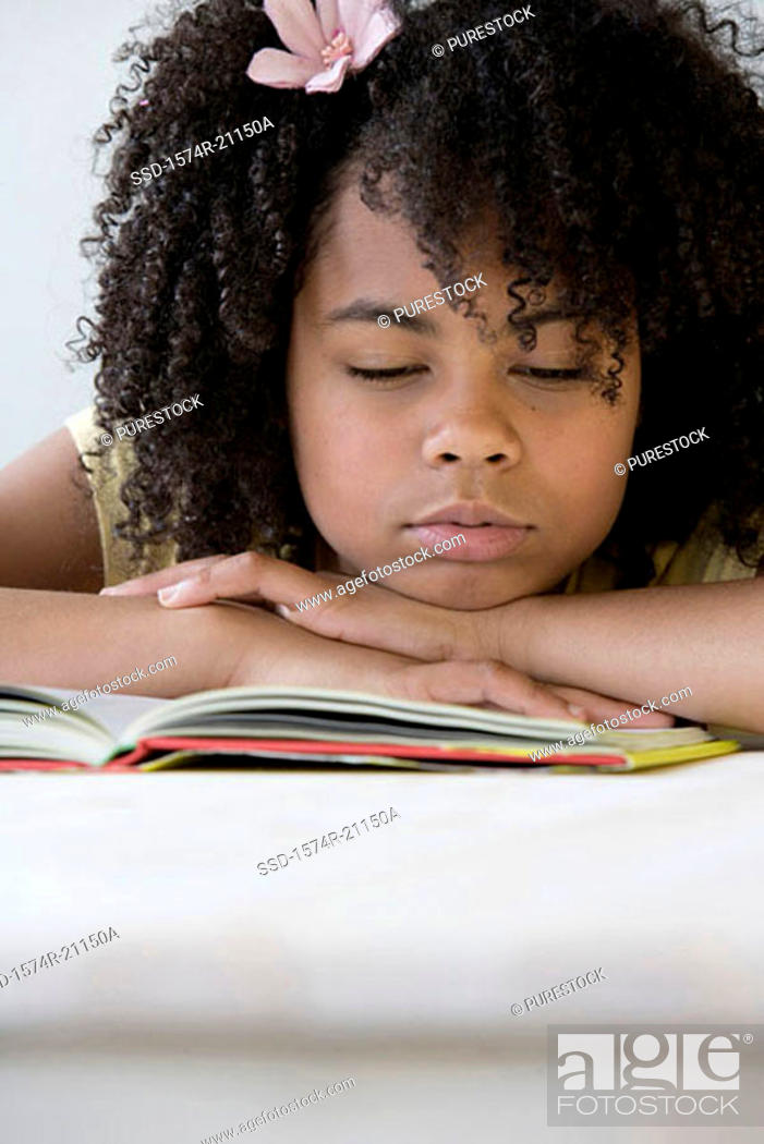 Stock Photo: Close-up of a girl sleeping on a book.