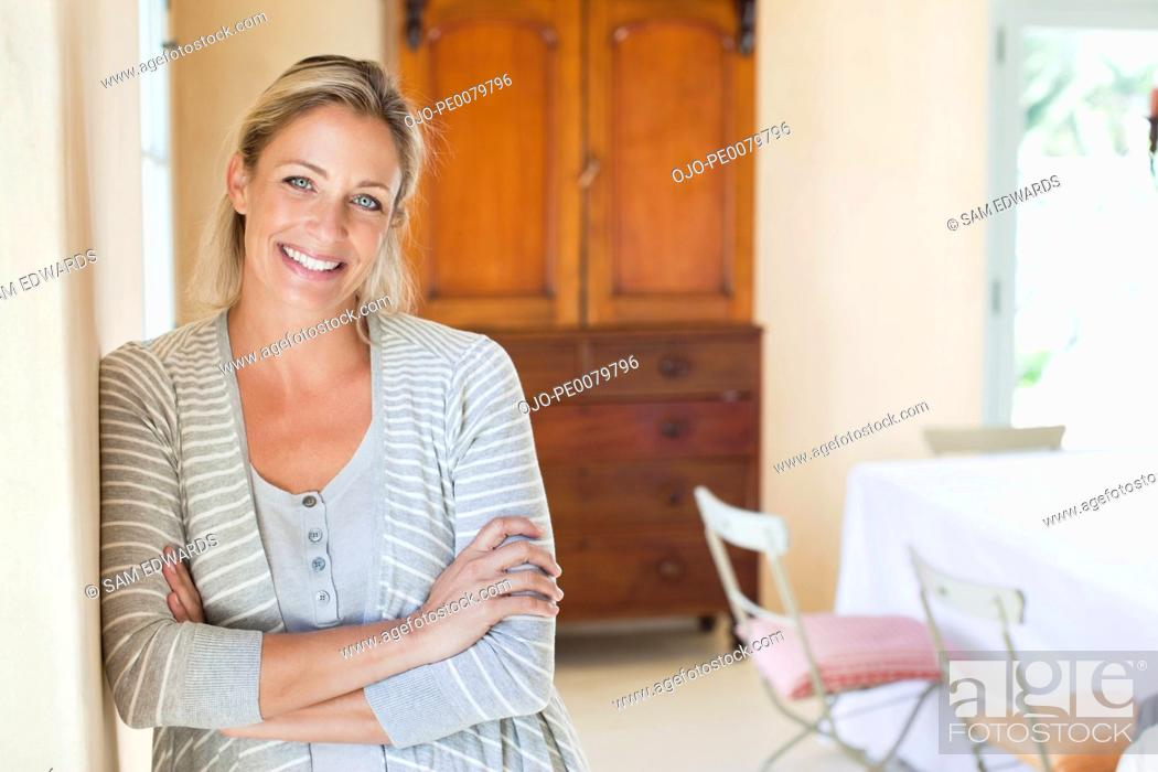 Stock Photo: Portrait of smiling woman leaning against wall with arms crossed.