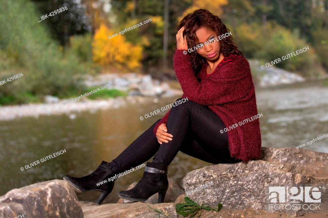 Stock Photo: Dark-skinned young woman with belly top in autumn forest.
