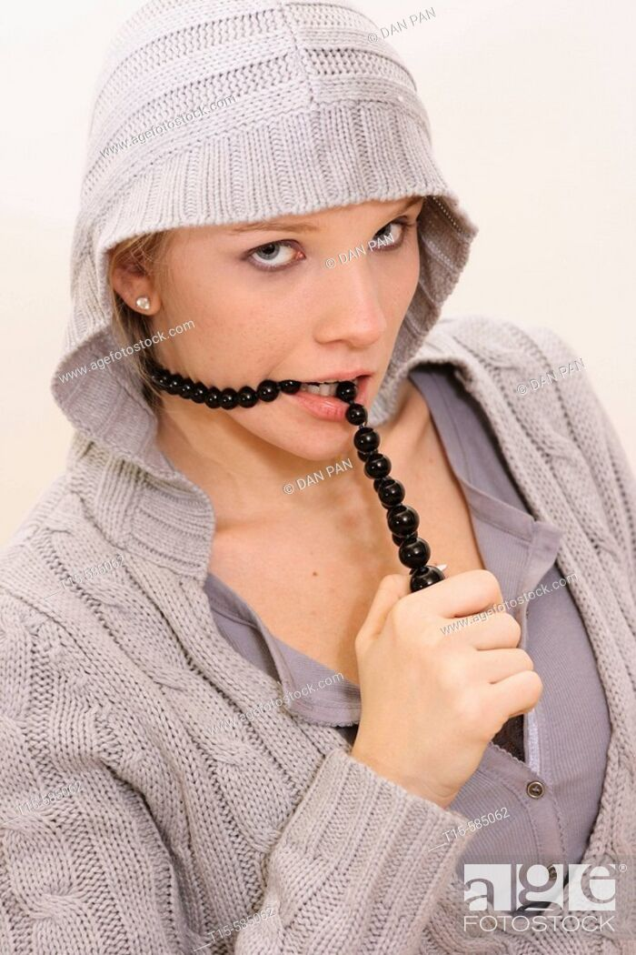 Stock Photo: young woman dressed in a blue gray hooded sweater wearing a black beaded necklace and biting on the necklace looking playful or bored.