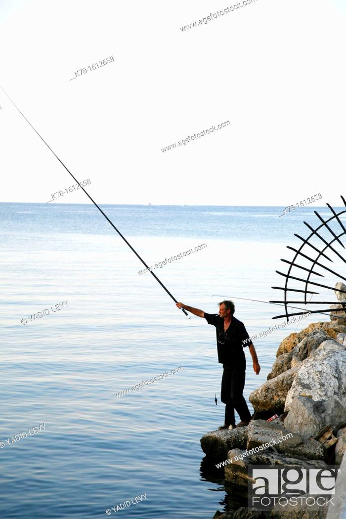 Stock Photo: Fisherman at the port outside Rhodes old Town, Rhodes, Greece.