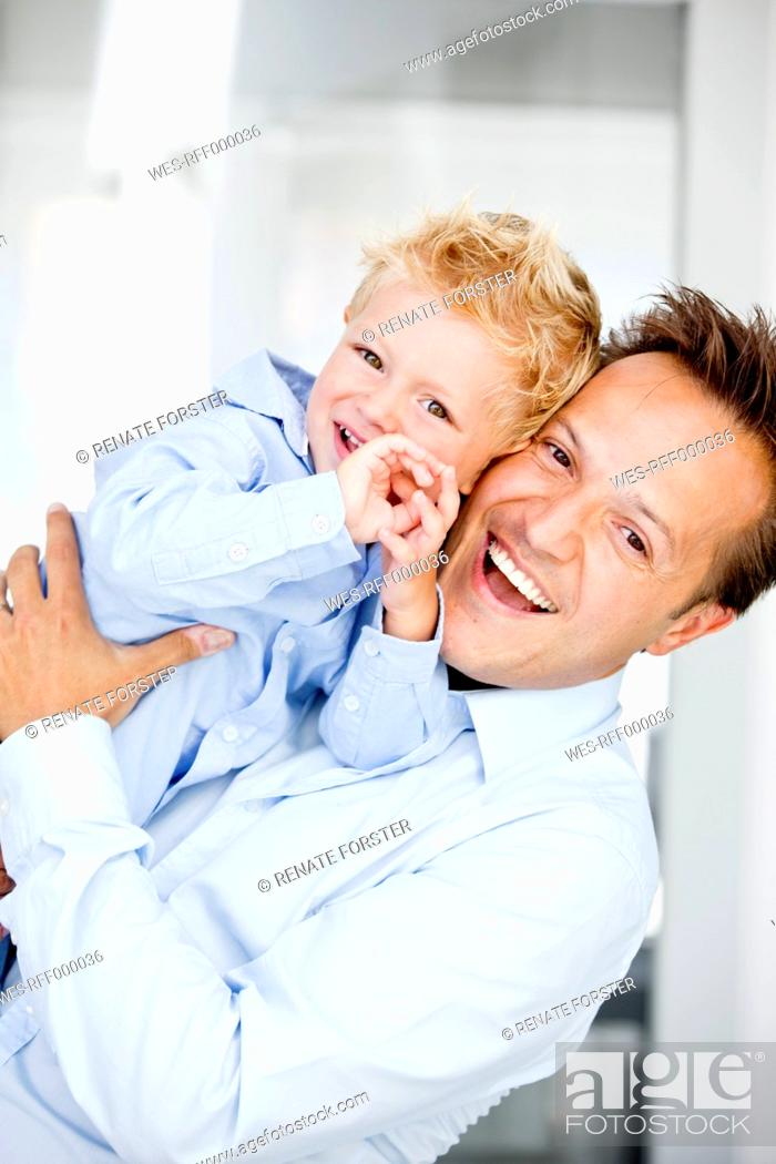 Stock Photo: Germany, Father carrying son, smiling, portrait.