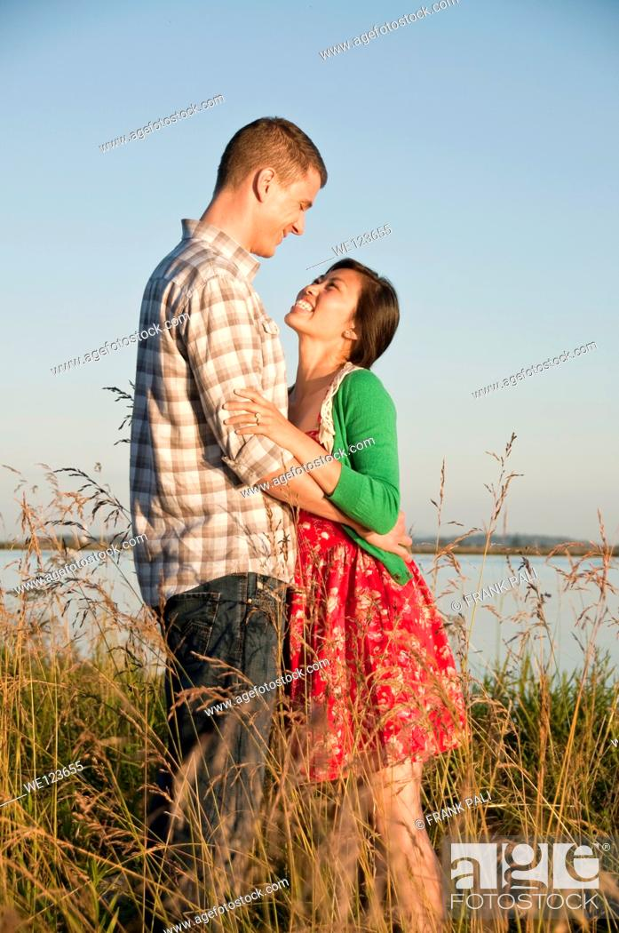 Imagen: Standing in tall grass is a mixed race couple arm in arm.