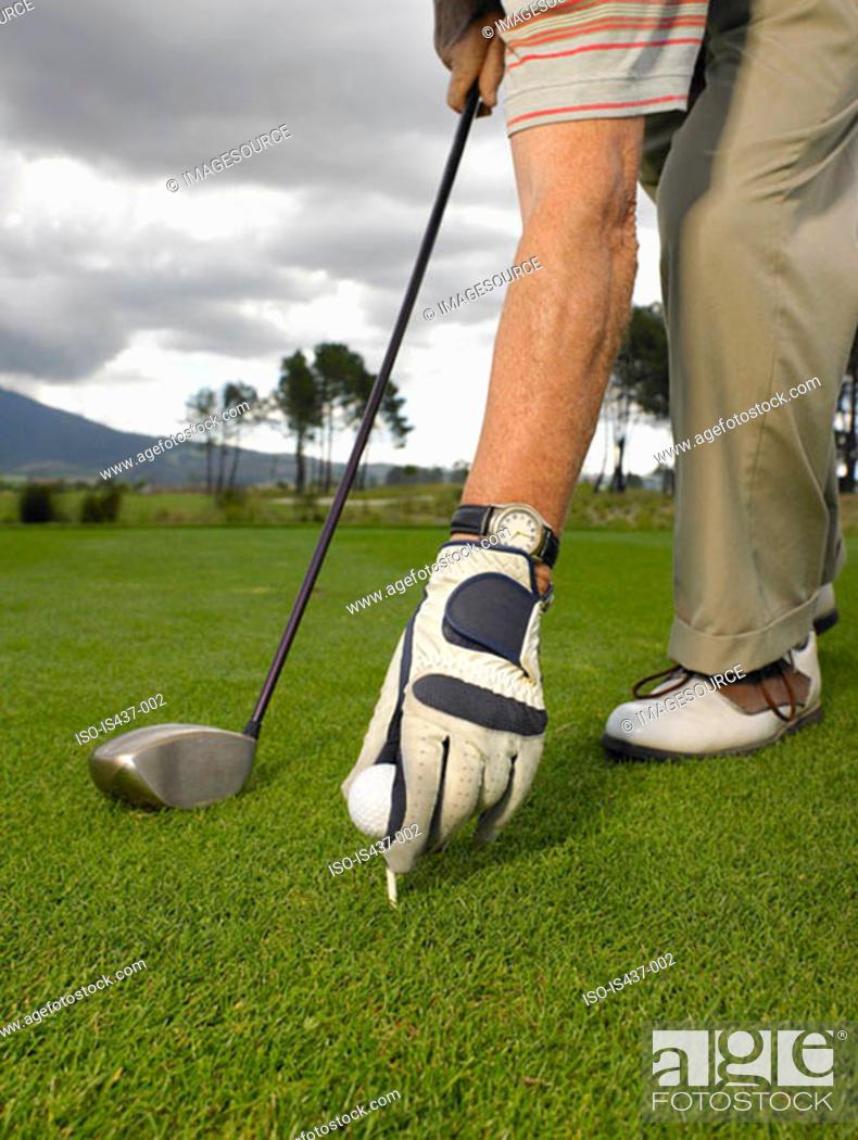 Stock Photo: Man placing golf ball on tee.