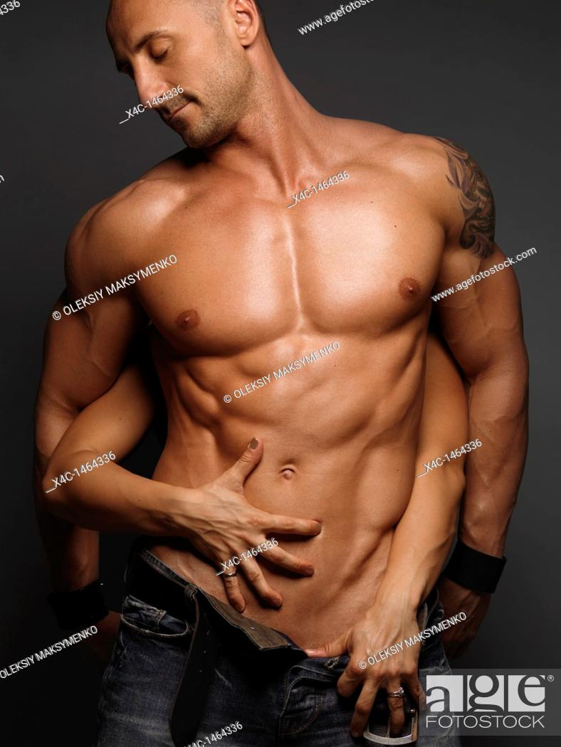 Stock Photo: Woman's hands touching young muscular man's body.